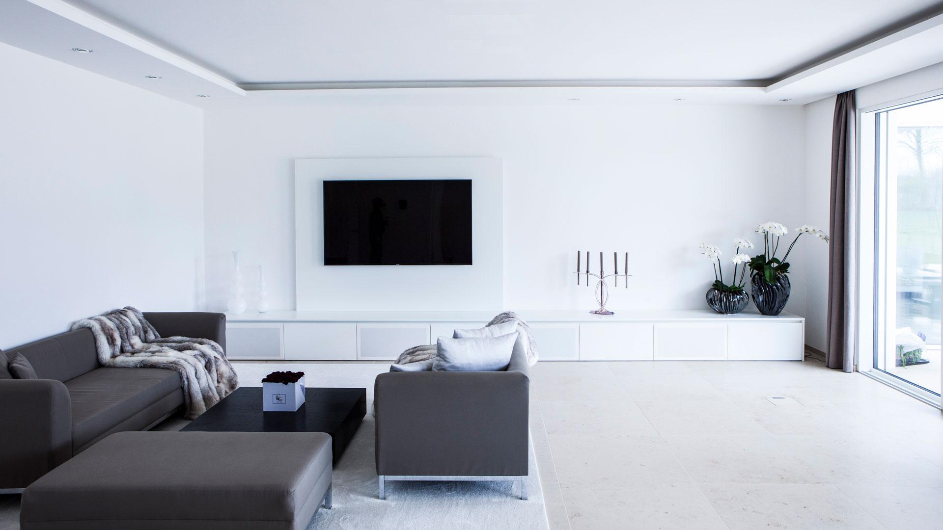 Wohnzimmer in weiß mit großem TV-Schrank und integriertem Soundsystem